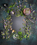 Infusión de hierbas en el fondo blanco Diversas hierbas, herramientas del té y taza frescas de té en el fondo oscuro del vintage, imágenes de archivo libres de regalías