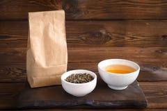 Infusión de hierbas en taza Una bolsa de papel de hierbas y de una taza de bebida caliente Fondo de madera imagenes de archivo