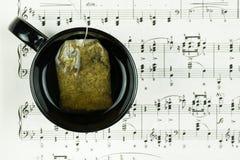 Infusión de hierbas y bolsita de té en la situación negra de la taza en la hoja con las notas musicales como fondo foto de archivo