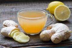 Infusión hecha en casa del té del jengibre en el tablero de madera con el limón Fotos de archivo