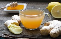 Infusión hecha en casa del té del jengibre en el tablero de madera con el limón Fotos de archivo libres de regalías