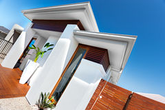 Ingång av ett lyxigt hus med vita väggar och blå himmel på en su royaltyfria bilder