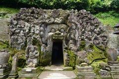 Ingång av grottan till och med den sned munsneda bollen som är öppen i Bali Indonesien Arkivbilder