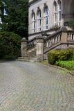 Ingång med trappa och kullerstengator arkivbild