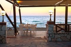 Ingång som tömmer kafét på den sandiga stranden på solnedgången Begrepp av loppet och semestern Sammetsäsong arkivfoto