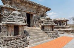 Ingång till byggnader för forntida tempel av Halebidu, med sned väggar av den 12th århundradeHoysaleshwara templet, Indien Royaltyfri Foto