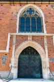 Ingång till den massiva tegelstenkatolska kyrkan Royaltyfri Bild