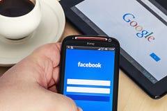 Ingång till den sociala nätverksfacebooken via mobiltelefonen HTC. Arkivfoton