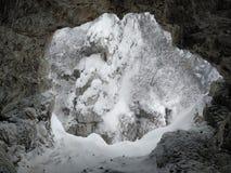 Ingång till en grotta som täckas i snö arkivbild