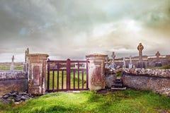 Ingången till kyrkogården med metallportar och betong fäktar arkivfoto