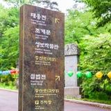 Ingångsbana med tecknet till den koreanska buddistiska templet Beomeosa på en dimmig dag Lokaliserat i Geumjeong, Busan, Sydkorea royaltyfri foto