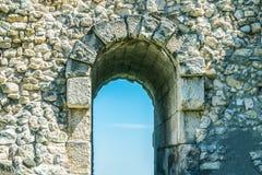 Ingångsdörröppningen i stenar väggen, bågen för ingång, och utgången i fördärvar av den gamla staden royaltyfria bilder