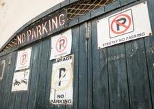 Ingångsport med mycket olikt parkera inte tecken och märka arkivbild