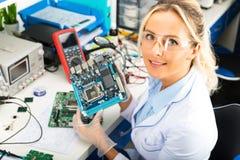 Ingénieur électronicien féminin tenant la carte mère d'ordinateur dans des mains Image stock