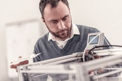 Ingénieur adulte futé fixant une imprimante 3D photographie stock libre de droits