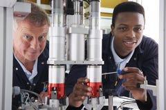 Ingénieur And Apprentice Working sur la machine dans l'usine Images stock