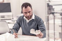 Ingénieur assidu comparant ses dessins à la disposition photo stock