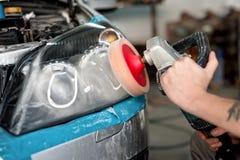 Ingénieur automobile polissant le phare d'une voiture Image libre de droits