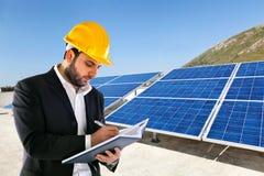 Ingénieur avec de grands panneaux solaires sur le fond images libres de droits