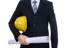 Ingénieur avec le plan jaune de casque et de papier Image stock