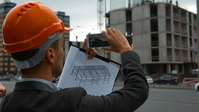 Ingénieur avec le téléphone intelligent prenant des photos de construction banque de vidéos