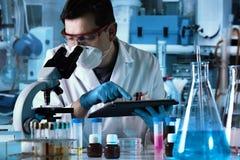 Ingénieur biochimique travaillant avec le microscope et le comprimé dans le l photos libres de droits