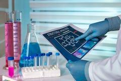 Ingénieur chimiste travaillant avec l'information dans le laborato de chimie photographie stock libre de droits