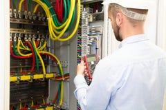 Ingénieur d'électricien avec les travaux de mesure d'outil photographie stock
