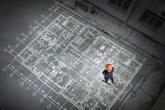 Ingénieur d'homme pensant au-dessus de son plan Media mélangé photographie stock