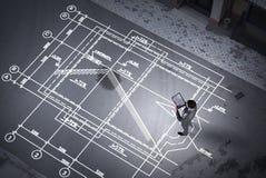 Ingénieur d'homme pensant au-dessus de son plan Media mélangé photos stock