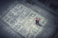 Ingénieur d'homme pensant au-dessus de son plan Media mélangé photographie stock libre de droits