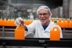 Ingénieur d'usine examinant une bouteille de jus Photo stock