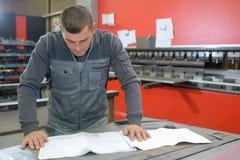 Ingénieur dans des instructions mécaniques de lecture d'usine photographie stock libre de droits