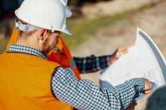 Ingénieur dans le casque blanc consultant sur le plan de projet avec l'escroquerie photos libres de droits