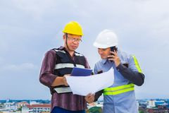 Ingénieur de construction asiatique travaillant avec son agent de maîtrise tout en employant photos stock