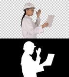 Ingénieur de femme avec le comprimé faisant l'appel visuel, Alpha Channel photographie stock libre de droits