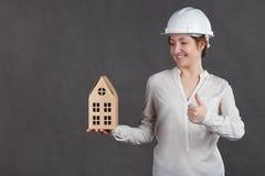 Ingénieur de jeune femme dans le casque de protection avec la maquette dans des mains Photos stock