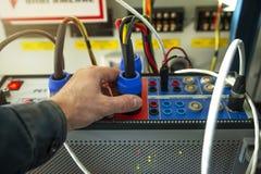Ingénieur de technicien d'électricien avec le dispositif d'essai pour examiner des protections de relais des lignes de haute tens image stock