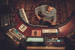 Ingénieur du son avec la guitare fonctionnant dans le studio d'enregistrement de boutique Photo libre de droits