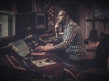 Ingénieur du son travaillant au panneau de mélange dans le studio d'enregistrement de boutique Photographie stock