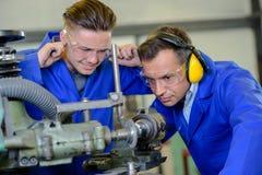 Ingénieur employant l'apprenti de machine avec des doigts dans des oreilles Photos libres de droits