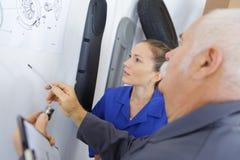 Ingénieur et apprenti féminin travaillant à la structure de conception Photographie stock