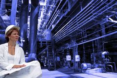 Ingénieur féminin avec des modèles sur l'usine Image stock