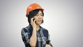 Ingénieur féminin avec le casque orange ayant un appel téléphonique par l'intermédiaire du smartphone sur le fond blanc clips vidéos