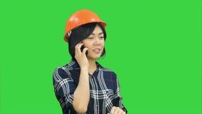 Ingénieur féminin avec le casque orange ayant un appel téléphonique par l'intermédiaire du smartphone sur un écran vert, clé de c banque de vidéos