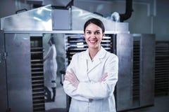 Ingénieur féminin de sourire devant la machine de déshydrateur de dessiccateur de nourriture photo stock