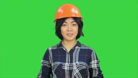Ingénieur féminin se tenant et parlant à un appareil-photo sur un écran vert, clé de chroma clips vidéos