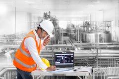 Ingénieur industriel vérifiant le statut de machine avec l'ordinateur portable image libre de droits