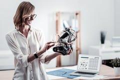 Ingénieur joyeux vérifiant vers le haut de son robot Photos stock