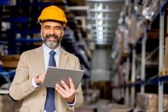 Ingénieur mûr dans l'entrepôt avec le comprimé numérique image libre de droits